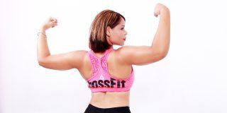 jeune femme corpulente lève les mains à la manière des bodybuilders